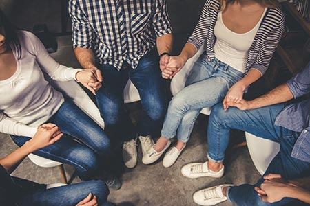 Teens holding hands at support group meeting
