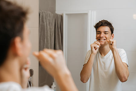 Teen boy flossing in mirror