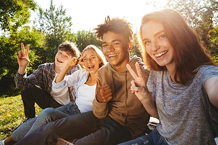 Group of teens smiling at the camera with hands in the shape of peace signs